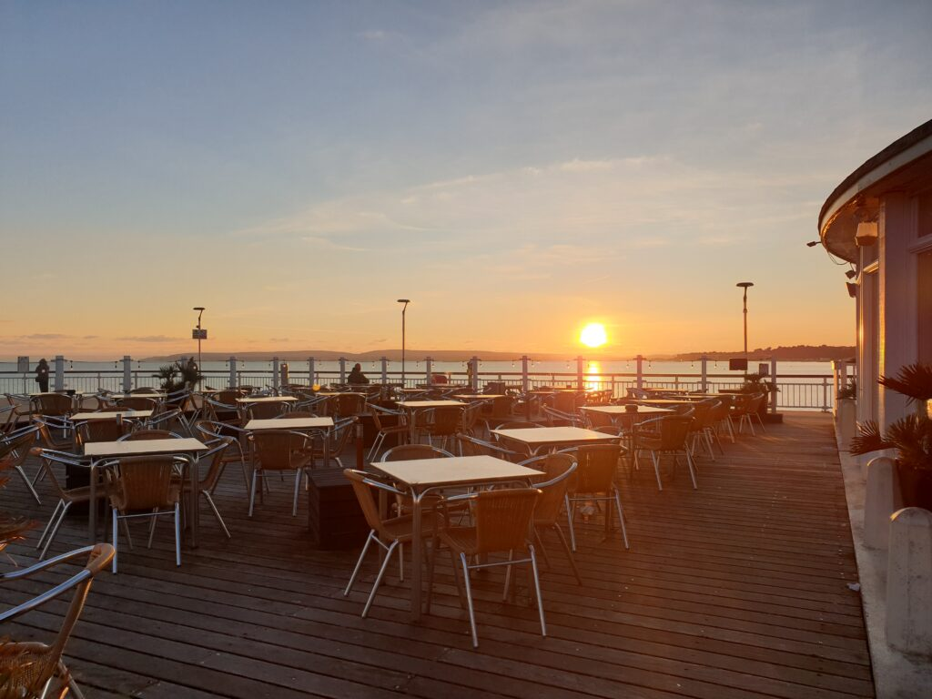 Large sun terrace with tables and seating on Bournemouth pier. Sun setting over sea perfect for sundowner sessions